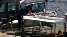 Sports Fisherman  At  A Fish Cleaning Station