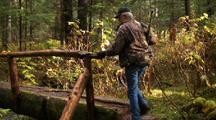 A Hunter On A Log Footbridge