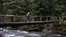 A Hiker/Hunter Crossing A Stream On A Log Footbridge