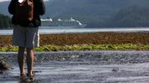 Person Watching Fish In A Stream, Cruise Ship In Distance