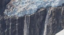Aerial Cineflex Tilt Down Hanging Glacier To Waterfalls Water Cascading Down Rocky Cliff Face