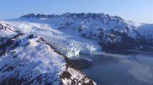 Aerial Cineflex Flight Over Snow Covered Coastal Mountains Toward Tidewater Glacier Spilling Into Fjord