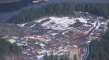Aerial Cineflex Travel Over Logging Operation Stacks Of Timber In Coastal Mountains Near Inside Passage