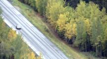 Lone Car Drives Along Road (Pull Back) That Cuts Through Boreal Forest Taiga Of Interior Alaska, Late Summer Early Fall Autumn Colors. Zatzworks Cineflex Aerial Photography.