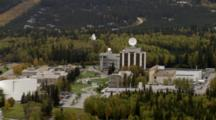 Large Satellite Dish Atop Building, Pull Back Reveal Uaf University Of Alaska Fairbanks Campus Surrounded By Boreal Forest. Cineflex Aerial Of Alaska By Zatzworks