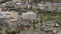 Footbridge Across River Connects Downtown Parks, Pull Back To Reveal Fairbanks Alaska Metropolis. Cineflex Aerial Of Alaska By Zatzworks