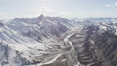 Slow Aerial,Grand Vista of Expansive snow-Covered Mountain Range with Frozen River