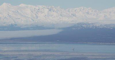 Oil Platform in Vast,Barren Alaska Landscape,Mountain Range Behind