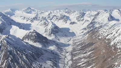 Slow Aerial Grand Vista of Snow-Covered Rugged Mountain Range