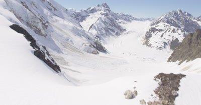 Aerial Through Snow-Covered Mountains of Alaska,Over Ridge to Reveal Grand Vista