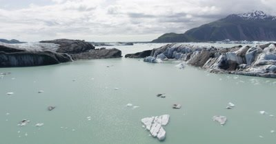Low POV Aerial Over Icebergs,Tilt To Reveal Wide View of Area