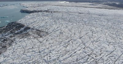 Low Aerial Over Glacier,Ice Field on Coast Alaska with patterns and debris