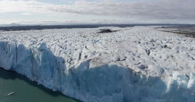 Aerial Toward and Over Steep Edge of Coastal Glacier to Wide View Over Ice