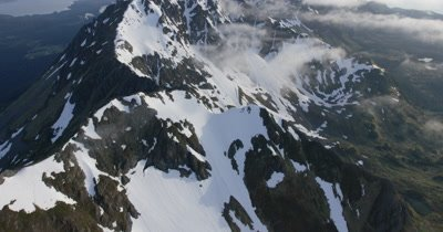 Low POV Aerial Along Jagged,Snow-Covered Ridge of Alaska Range