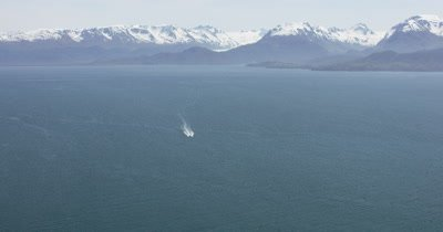 Very Wide Aerial Single Motor Boat Travels in Open Water,Mountain Range in Distance