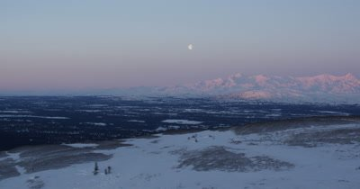 Grand Expansive Vista of Moon Above Alaska Winter Landscape at Sunrise or Sunset