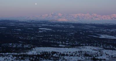Grand Expansive Vista of Moon Above Alaska Winter Landscape at Sunrise or Sunset