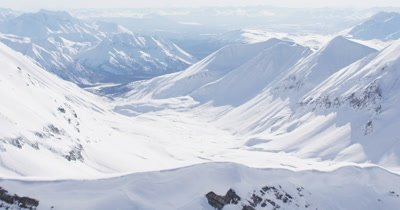 Aerial over Ridge to Reveal Grand Vista of Alaska Mountain Range Covered in Snow