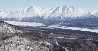Aerial View of Wide Valley,Frozen river,Roads with Snow-Capped Mountain Range Behind