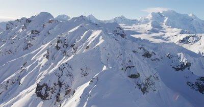 Low POV Aerial Over Ridge,Reveal Grand,Expansive Vista of Snow Covered Alaska Range