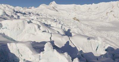 Very Low,POV Aerial Over Deep Chunky Snow,Crevices, Glacier,Tilt to Reveal Wide Vista