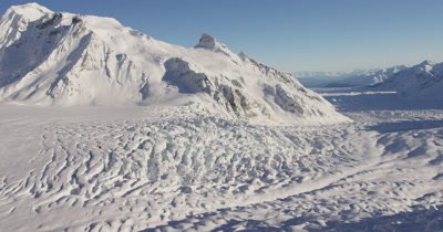 Very Low,POV Aerial Over Deep Chunky Snow,Crevices,Possibly Glacier,Tilt to Reveal Wide Vista