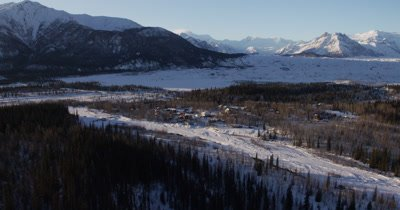 Low POV Aerial Over Coniferous Forest,Tilt to Reveal Wide,Expansive View of Snow-Covered Mountain Range,Pass Over Town of McCarthy