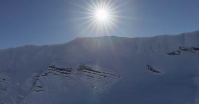 Aerial L Snow-Cooking up at sheer,snow-covered Mountains with Bright sun