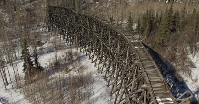 Aerial Following Old Abandoned Structure,Possibly Wooden Railroad Trestle in forest