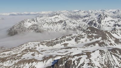 Slow Aerial,Grand Vista of Majestic Mountain Range with Low Clouds