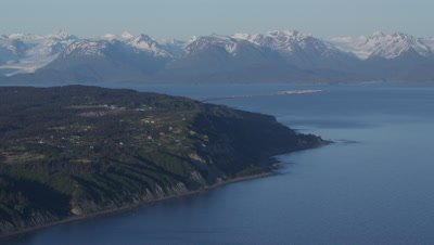 Aerial,Alaska Coastline,Houses on Bluff,Zoom out to Snow-capped Mountain Range