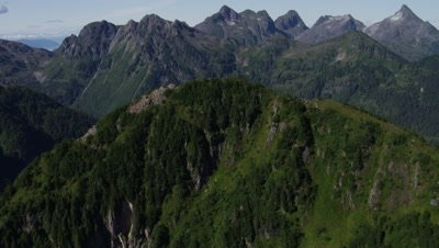Aerial Alaska over forested landscape to reveal rugged mountain range