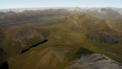 Aerial Alaska,Low Over Ridge To Reveal Vast Mountain Range,Dry River Bed