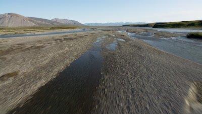 Aerial Alaska,POV Low over gravel river bed