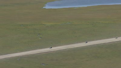 Aerial alaska,vehicles travel on empty dirt road,pull out to wide view of wetland and oil facilities