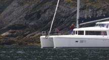 Catamaran Sail Boat Motors Along Coast In Front Of Temperate Coniferous Forest