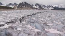 Cineflex Aerial Flight Low Altitude Over Beautiful Alaska Glacier Crags And Pools With Mountains At Side Of Moraine