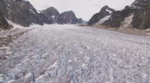 Exnice Low Altitude Cineflex Aerial Flight Over Alaska Glacier Forbidding Crags Ridges Brilliant Blue Fissures Tilt Up To Horizonal And Rocky Mountains Vertical Peaks On Edge Of Moraine