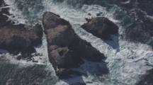 Slowly Circling Aerial Shot Pull From Waves Crashing On Rocks To Wider Shot Of Farallon Islands In Inky Sea