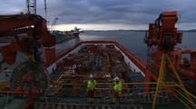 Workers Observe Loading Cargo Onto Oil Platform Supply Vessel