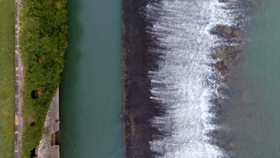Flying over a river dam, trees and kiwi fields