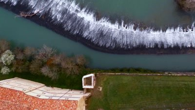 Flying over a village, a monastery and river dam