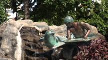 Statue Of Surfer & Monk Seal In Waikiki, People Walk By