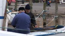 Fishermen On Small Fishing Boat Mend Their Nets, Dragor Denmark, Marina In Background, Shot Zooms Out