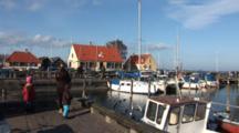 Family Feeds The Ducks And Gulls In The Small Marina In DragøR, Denmark, Near CøPenhagen