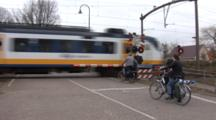 A Commuter Train In Holland Passes Camera At Speed.  Bicyclists Stopped At Crossing.