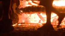 A Large Campfire Close Up At Ground Level, People Walk Through Frame.