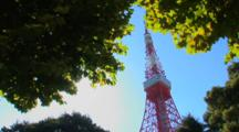 Tokyo, Japan - The Tokyo Tower In The Shiba Neighborhood, Framed By Trees With Sunburst, Pan To Right