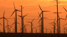 Wind Turbine Farm In Silhouette Against The Morning Light In The California Desert, Low Angle, Shot Includes Transmission Lines And Towers, Zoom Out