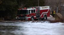 Major Flooding In A Small New England Town, River Has Overflowed A Road, Emergency Vehicles In Background Pumping Water From A Home, River In Forground, Zoom